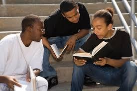 three young men studying the Bible outside